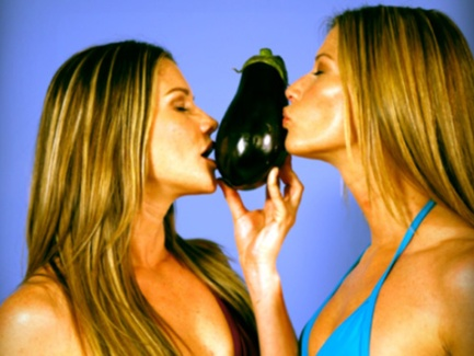 two girls in bikinis kissing an eggplant