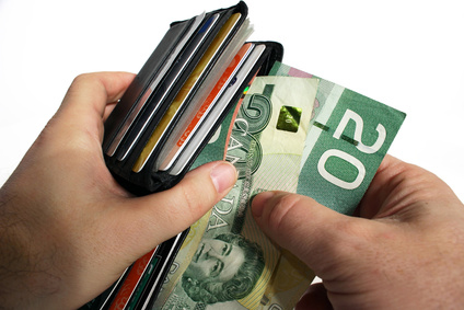 The action of pulling canadian money out of a wallet.