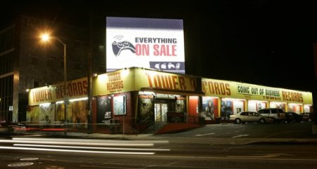 The headlights of cars are blurred in this time-exposure photo of Tower Records in West Hollywood, Calif., Wednesday, Oct. 11, 2006. Tower Records is in the midst of a liquidation sale to clear their shelves before the chain closes their door. After the close of the auction of the record seller's assets Friday, a federal bankruptcy judge approved the sale of California-based Tower Records to the Great American Group, which plans to liquidate the music retailer. (AP Photo/Kevork Djansezian)